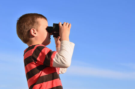 schoolkid search: Little boy observing surroundings in midday
