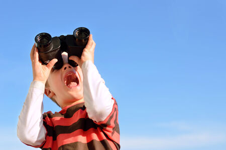 Surprised boy with binoculars against blue sky Stock Photo