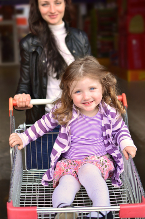 Joyful little girl sitting in an empty shopping cart driven by young mother photo