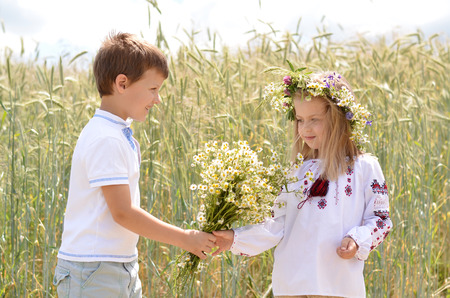 Romantic boy giving flowers to beautiful girl against wheat background in summer