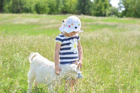 happy young: Ni�a y joven cabra blanca en verano