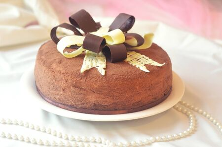 recipe decorated: Brown cake decorated with black and white chocolate bow