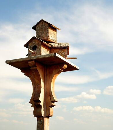 A wooden birdhouse on top of a pole with clouds in the background Stock Photo - 7776801