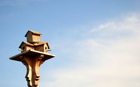 A wooden birdhouse on top of a pole with clouds in the background photo