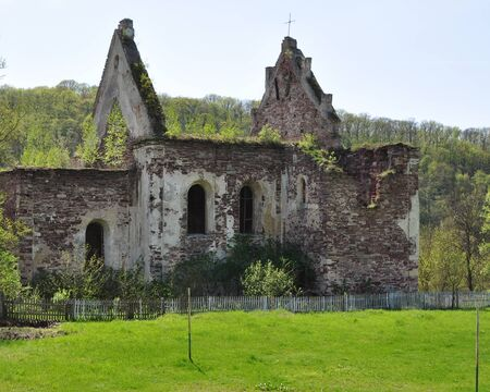 An old destroyed brick building with broken arched windows. From the roof were only gables. Against the background of a glade of young juicy spring grass under the sun.
