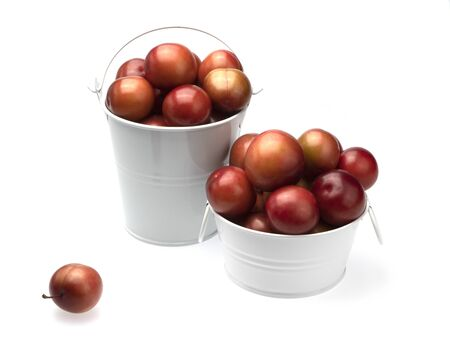 Ripe maroon plums in a white basin with round handles, a white bucket with a handle and one dropped out near it on a white background. Isolated. Close-up. Still life. 写真素材 - 131980862