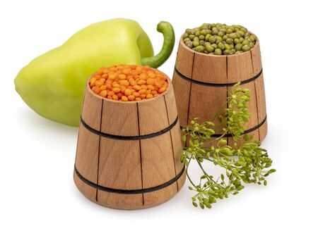 Lentils and mung beans in wooden buckets. Green pepper. Inflorescence, dill umbrella. Legumes. Grain in wooden tubs. On a white background, isolated. Still life. Close-up. 写真素材 - 131981814