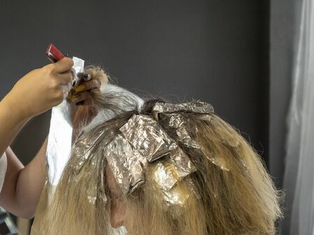 Hair highlights. Hairdressing. Comb and foil in the hands of a hairdresser. Wrapping strands in foil. Bleaching hair. Beauty saloon.