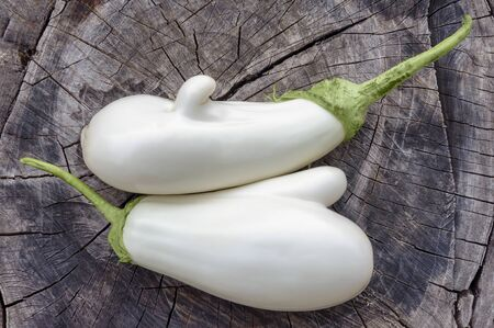 Two white eggplant lie on an old stump. Unusual nightshade. Still life. Close-up.