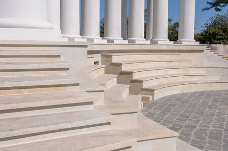 Staircase and colonnade. Marble white steps. Staircase at the base of the columns. Rhythm.