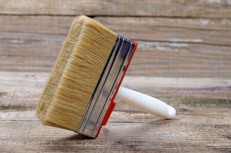 Building brush. Primer construction tool. Still life on old boards.
