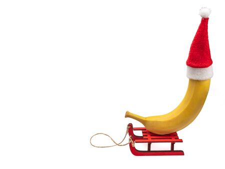 A banana in a red Santa Claus Christmas hat sits on a sled. Banana in a New Years suit. Masquerade for a banana. Still life on a white background, isolated.
