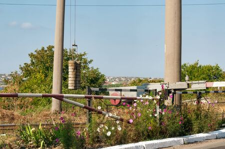 Barrier on railway by a sunny day. Flowers near the road. Rural railway.