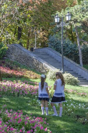 Warm autumn day. Young elegant schoolgirls are walking in the park. Stairs, lanterns, flower beds and lawns adorn the area.