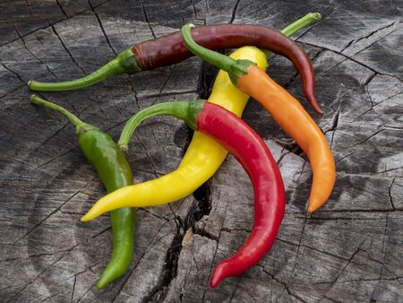 Chilli. Multi-colored pepper. A lot lies on the old stump. Food, ingredient, seasoning. Still life. Close-up.