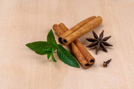 Fragrant spices on a light tree. Cinnamon sticks, star anise stars, clove buds and green mint leaves. Still life close up view. Stockfoto