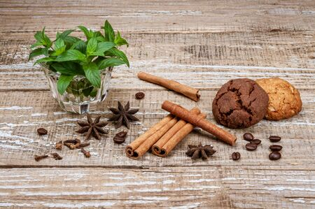 Fragrant spices, mint and coffee beans. Oatmeal and chocolate homemade cookies on a wooden background. Coffee grains, cinnamon sticks, clove buds, star anise anise flowers and green mint leaves in a glass bowl. Still life close up view. Stockfoto