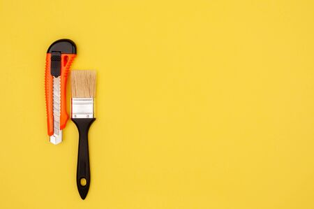 Brush and knife painter on a yellow background. The tool for the job.