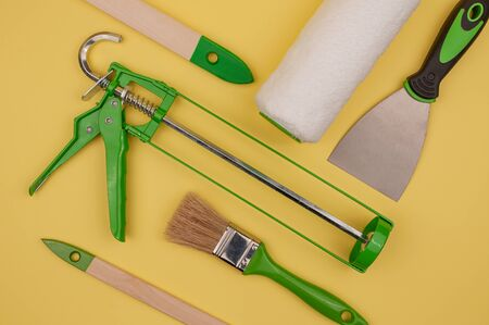Green paint hand tool on a yellow background. Brush and putty knife, paint roller and gun.