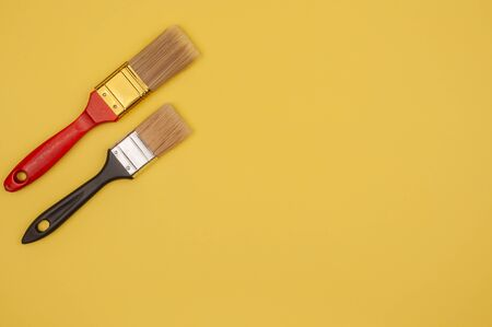 Paint brush on yellow background. The tool of the painter. Natural and artificial bristles.
