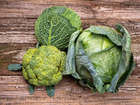 Three kinds of cabbage on old wooden background. Cabbage cuts closeup view. Savoy, broccoli, cabbage.