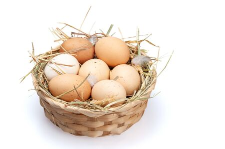 Chicken eggs in a basket with hay. Organic eggs on a white background. Banco de Imagens