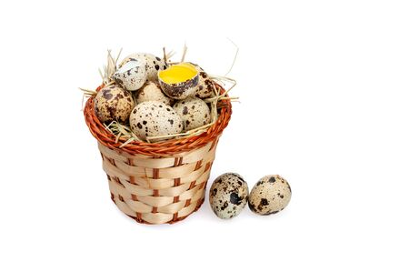 Quail eggs in a basket and near it on a white background. The yolk in a broken eggshell. Two eggs lie near the basket.