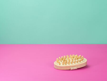 Massage brush, bathroom accessories on pink and turquoise background. The view from the top. Standard-Bild