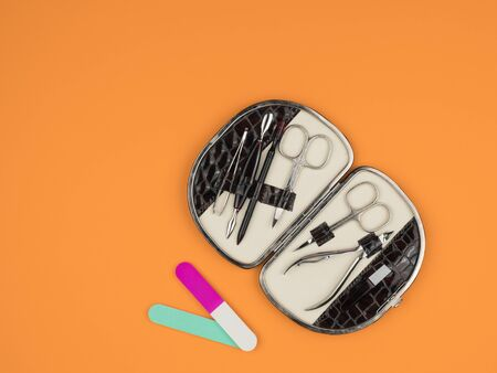 Kit accessories for manicure on orange background. Pink and turquoise nail files.