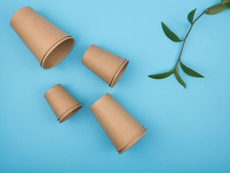Stylish recyclable paper tableware on a blue background. The view from the top. Disposable cups. 版權商用圖片