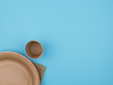 A paper plate and a glass on a blue background. The view from the top. Napkin of burlap. Cardboard tableware.
