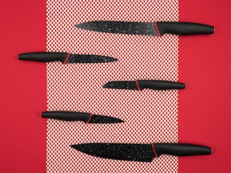 A set of kitchen knives on a white doily on a red background. The view from the top.