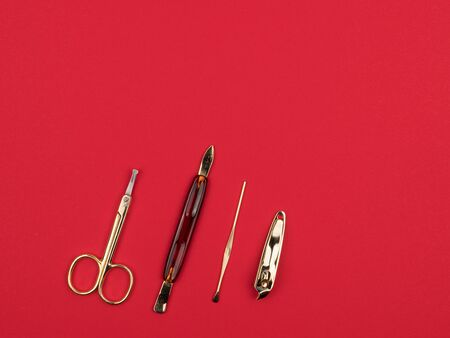 Golden manicure set on a red background. The view from the top. Scissors and other accessories.