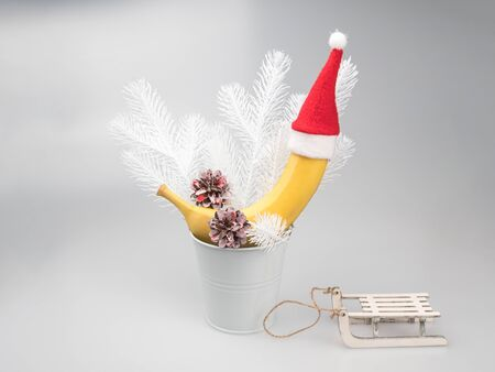 Banana in the Santa hat. White winter decorative accessories. Banco de Imagens