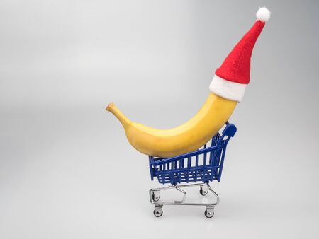 Banana in the Santa hat on the mini cart from the supermarket.