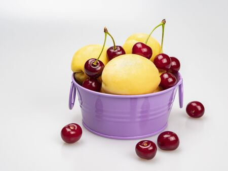Yellow apricots and ripe cherries in a lilac bowl and near, on a white background.