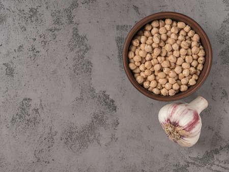 Chickpeas and garlic closeup. The gray background. Reklamní fotografie