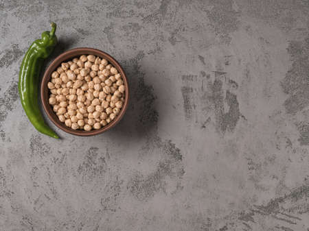 Chickpeas in a bowl and selenay chilli. The gray background. Reklamní fotografie