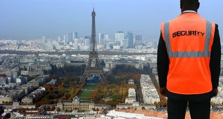 undercover agent: Security agent watching Paris from hilltop Stock Photo