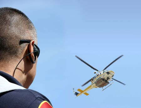 Security agent coordinating surveillance with helicopter