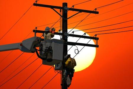 Utilidad de trabajadores reparación una línea de energía al atardecer