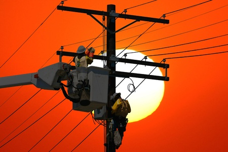Utility workers repair a power line at sunset