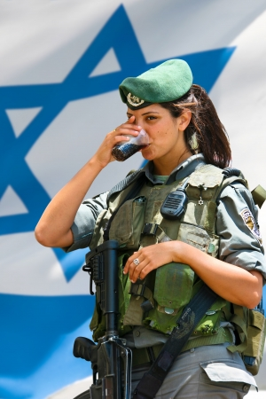 JERUSALEM, ISRAEL - MAY 30, 2011: Unidentified Israeli army girl drinks Coca-Cola at the Israel Expo, one of the largest celebration of Israel culture on May 30, 2011 in Jerusalem, Israel **************** Jerusalem, Israel - May 30, 2011: Israeli army gir photo