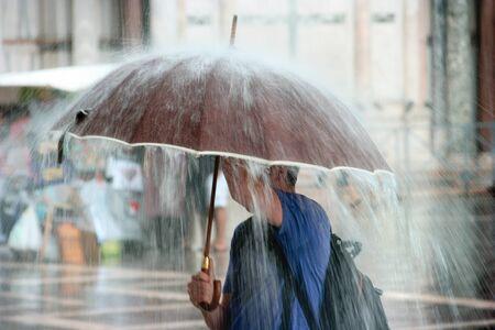 uomo sotto la pioggia: Forti piogge in città Archivio Fotografico