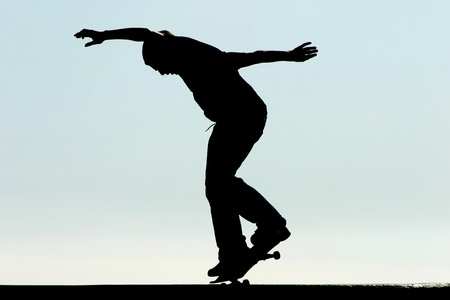 skateboarding tricks: Male skateboarder jumps on a concrete edge at a skateboard park