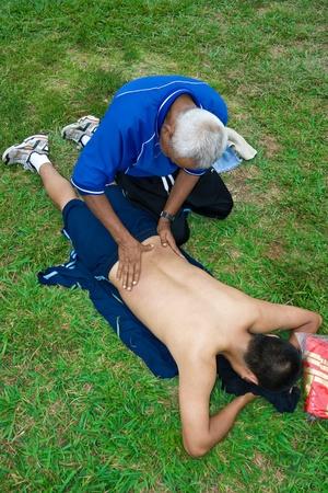 performs: Medico sportivo esegue massaggi nel campo di calcio