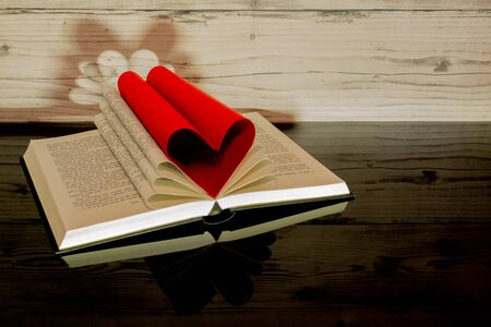 Book folded in the shape of a heart on a wooden background.