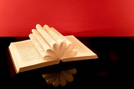 Book folded in the shape of a heart on a red background.