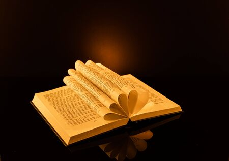 Book folded in the shape of a heart on a black background. Stock Photo