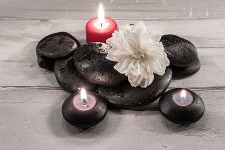 Black pebbles with water drops and candles.